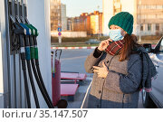 A woman with protective mask remembers brand of fuel at a gas station for her car. Looking at several nozzles with regular petrol and diesel. Стоковое фото, фотограф Кекяляйнен Андрей / Фотобанк Лори