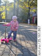 Little beautiful girl riding scooter in park. Стоковое фото, фотограф Арестов Андрей Павлович / Фотобанк Лори