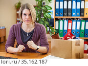 Employee woman is absolutely furious about lost her job, sitting in workplace with carton box with things. Стоковое фото, фотограф Кекяляйнен Андрей / Фотобанк Лори