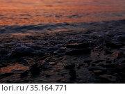 Surf on rocky beach at dusk with sunset reflection on waves. Стоковое фото, фотограф Евгений Харитонов / Фотобанк Лори