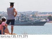 Моряк смотрит парад в честь Дня ВМФ с северной стороны Севастопольской бухты, Крым (2020 год). Редакционное фото, фотограф Николай Мухорин / Фотобанк Лори