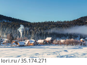 Winter landscape with the village of Iogach on the background of forested mountains. Altai Republic, Russia. Стоковое фото, фотограф Наталья Волкова / Фотобанк Лори