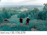man and woman tourists stand on a mountainside and admire the beauty of the Ural taiga on a summer day. Стоковое фото, фотограф Акиньшин Владимир / Фотобанк Лори
