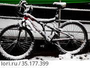 Велосипед весь в выпавшем снегу стоит у входа в магазин в городе Москве, Россия. Редакционное фото, фотограф Николай Винокуров / Фотобанк Лори