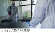 Team of health workers wearing protective clothes cleaning the office using disinfectant sprayer. Стоковое видео, агентство Wavebreak Media / Фотобанк Лори