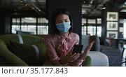 Asian woman wearing face mask having a video chat on smartphone at modern office. Стоковое видео, агентство Wavebreak Media / Фотобанк Лори