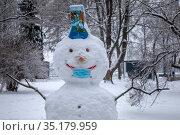 Снеговик с надетой медицинской маской стоит в парке города Москвы, Россия. Редакционное фото, фотограф Николай Винокуров / Фотобанк Лори