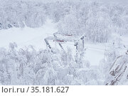 End station of the ski lift on a snow-covered hilltop among frosty trees. Стоковое фото, фотограф Евгений Харитонов / Фотобанк Лори