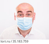 portrait of bald adult elderly man in medical mask with emotions on white background. Стоковое фото, фотограф Татьяна Яцевич / Фотобанк Лори