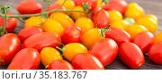 ripe appetizing yellow and red cherry tomatoes on wooden table. Стоковое фото, фотограф Татьяна Яцевич / Фотобанк Лори
