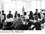Speaker giving a talk in conference hall at business meeting event. Rear view of unrecognizable people in audience at the conference hall. Стоковое фото, фотограф Matej Kastelic / Фотобанк Лори