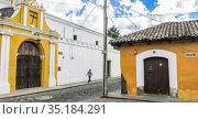 Yellow chapel church with crooked cross under blue  sky, Antigua, Guatemala. Редакционное фото, фотограф Николай Коржов / Фотобанк Лори