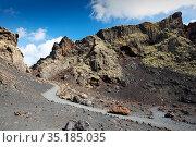 Footpath through volcanic soil and rocks inside Caldera de Los Cuervos volcano. Lanzarote, Canary Islands, Spain. November 2019. Стоковое фото, фотограф Ashley Cooper / Nature Picture Library / Фотобанк Лори