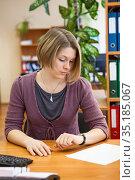 Administrative secretary timekeeping with wristwatch, woman sitting at table at work. Стоковое фото, фотограф Кекяляйнен Андрей / Фотобанк Лори