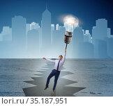 Businessman flying over gap on light bulb balloon. Стоковое фото, фотограф Elnur / Фотобанк Лори