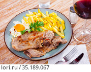 close up of grilled pork with fried potato and egg served on blue plate on wooden table. Стоковое фото, фотограф Яков Филимонов / Фотобанк Лори