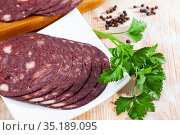 Close up of Spanish smoked blood sausage on white plate on wooden table. Стоковое фото, фотограф Яков Филимонов / Фотобанк Лори