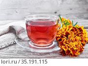 Чай травяной из бархатцев в стеклянной чашке на деревянной доске. Стоковое фото, фотограф Резеда Костылева / Фотобанк Лори