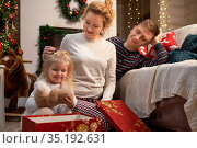 Happy young family celebrating Christmas at home by the fireplace. Стоковое фото, фотограф Алексей Кузнецов / Фотобанк Лори