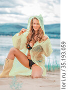 Portrait of a young beautiful woman in a swimsuit in a yellow raincoat and yellow rubber boots on a sandy beach on a summer day. Стоковое фото, фотограф Акиньшин Владимир / Фотобанк Лори