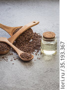 A jar of linseed oil flax seeds in a wooden spoon on a concrete background, a dietary cereal ingredient that reduces cholesterol, a source of omega-3, iodine, phosphorus, potassium, magnesium, nickel. Стоковое фото, фотограф Светлана Евграфова / Фотобанк Лори