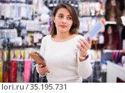 Positive young Latina choosing hairbrush in cosmetics store. Стоковое фото, фотограф Татьяна Яцевич / Фотобанк Лори