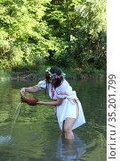 Девушка в национальной рубахе выливает воду из глиняного кувшина. Стоковое фото, фотограф Марина Володько / Фотобанк Лори