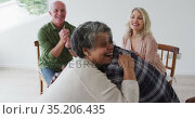 Two diverse senior couples sitting in circle having a therapy conversation at home. Стоковое видео, агентство Wavebreak Media / Фотобанк Лори