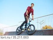 Bmx biker doing trick,teenager in skatepark. Стоковое фото, фотограф Tryapitsyn Sergiy / Фотобанк Лори