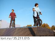 Bmx biker standing on ramp, training in skatepark. Стоковое фото, фотограф Tryapitsyn Sergiy / Фотобанк Лори