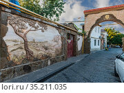 Yevpatoria Tuchina Street with a stone arch and a bas-relief on a residential building. Редакционное фото, фотограф Владимир Ушаров / Фотобанк Лори