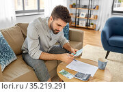man with money and calculator filling papers. Стоковое фото, фотограф Syda Productions / Фотобанк Лори