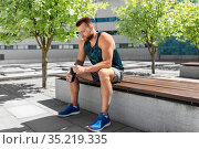 tired sportsman with bottle sitting on city bench. Стоковое фото, фотограф Syda Productions / Фотобанк Лори