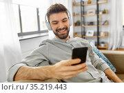 man in headphones listening to music on smartphone. Стоковое фото, фотограф Syda Productions / Фотобанк Лори