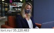 Caucasian businesswoman wearing face mask using laptop in modern office. Стоковое видео, агентство Wavebreak Media / Фотобанк Лори