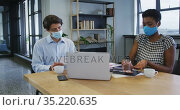 Diverse business collegues wearing face masks sitting using laptop going through paperwork in office. Стоковое видео, агентство Wavebreak Media / Фотобанк Лори