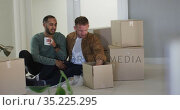 Multi ethnic male same sex couple drinking coffee and packing to move house. Стоковое видео, агентство Wavebreak Media / Фотобанк Лори