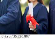 graduate students in mortar boards with diplomas. Стоковое фото, фотограф Syda Productions / Фотобанк Лори