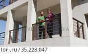 Multi ethnic gsy male couple drinking coffee on balcony in sun. Стоковое видео, агентство Wavebreak Media / Фотобанк Лори