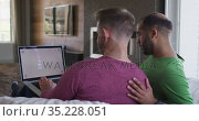 Multi ethnic gay male couple sitting on couch looking at laptop together. Стоковое видео, агентство Wavebreak Media / Фотобанк Лори