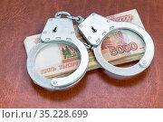 Наручники и деньги. Уголовное наказание за коррупцию. Стоковое фото, фотограф Наталья Осипова / Фотобанк Лори