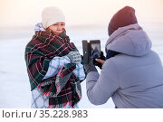 Girlfriend taking picture of posing woman with smartphone on winter lake in sunset light, girl wrapping with scarf. Стоковое фото, фотограф Кекяляйнен Андрей / Фотобанк Лори
