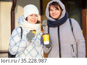 Two smilling woman portrait holding disposable paper cups with coffee in hands dressed mittens and gloves, winter season. Стоковое фото, фотограф Кекяляйнен Андрей / Фотобанк Лори