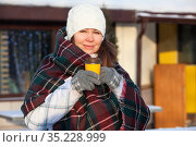 Caucasian woman in woollen gloves holds a paper cup of coffee in the winter city outdoors. Hot and warming beverage in the winter season. Стоковое фото, фотограф Кекяляйнен Андрей / Фотобанк Лори