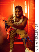 Stylish rapper shows his gold jewelry in studio. Стоковое фото, фотограф Tryapitsyn Sergiy / Фотобанк Лори