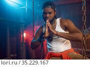 Stylish rapper poses near the chains in studio. Стоковое фото, фотограф Tryapitsyn Sergiy / Фотобанк Лори