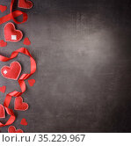 Bright scarlet ribbon and hearts made of handmade felt. Valentine's Day. Dark background. Стоковое фото, фотограф Сергей Молодиков / Фотобанк Лори