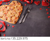 Romantic image. Pizza in the form of a heart, decor from red ribbon and heart. Top view. Blank space for inscription. Стоковое фото, фотограф Сергей Молодиков / Фотобанк Лори