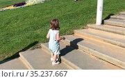 Toddler Caucasian girl wearing overall climbing on stone stairs outdoor, wide cement stairway up to hill. Стоковое видео, видеограф Кекяляйнен Андрей / Фотобанк Лори