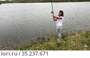 Happy woman with rod catching the small fish in lake, recreational fishing from the shore. Стоковое видео, видеограф Кекяляйнен Андрей / Фотобанк Лори